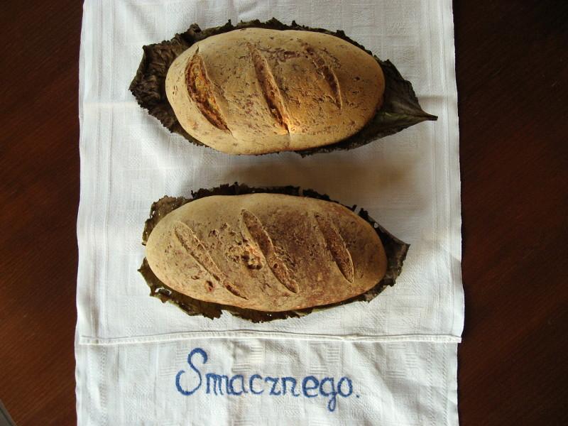 dwa chleby upieczone leżące na makatce z napisem Smacznego